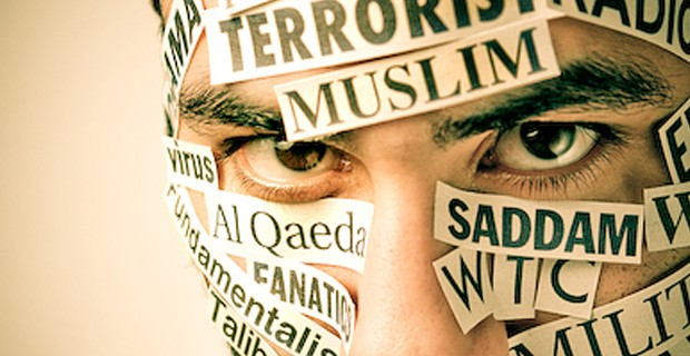 "a man with stickers covered all over his face, saying ""Saddam...al Qaeda...terrorism...fanatic...fundamentalist...Muslim"""