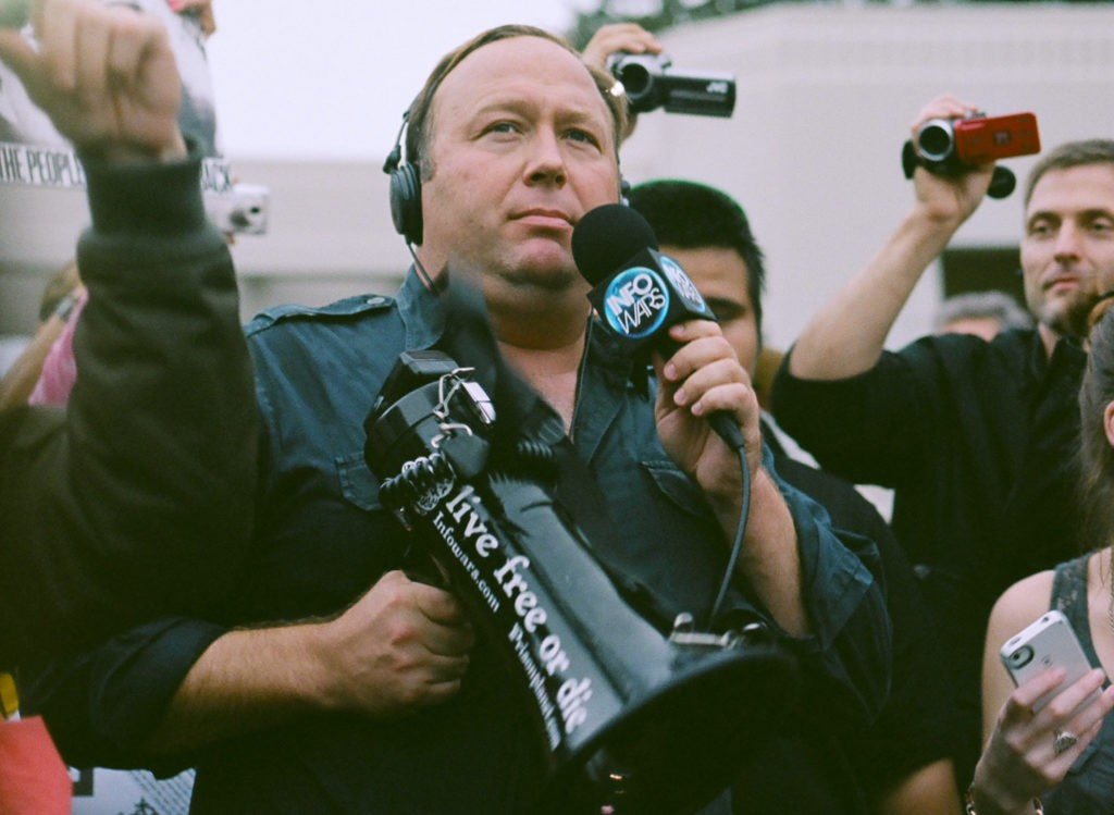 far right loudmouth Alex Jones is holding a speakerphone and a microphone at a protest