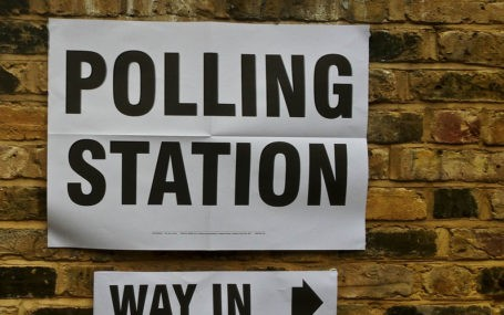 "A sign on a brick wall that says ""polling station - way in"""