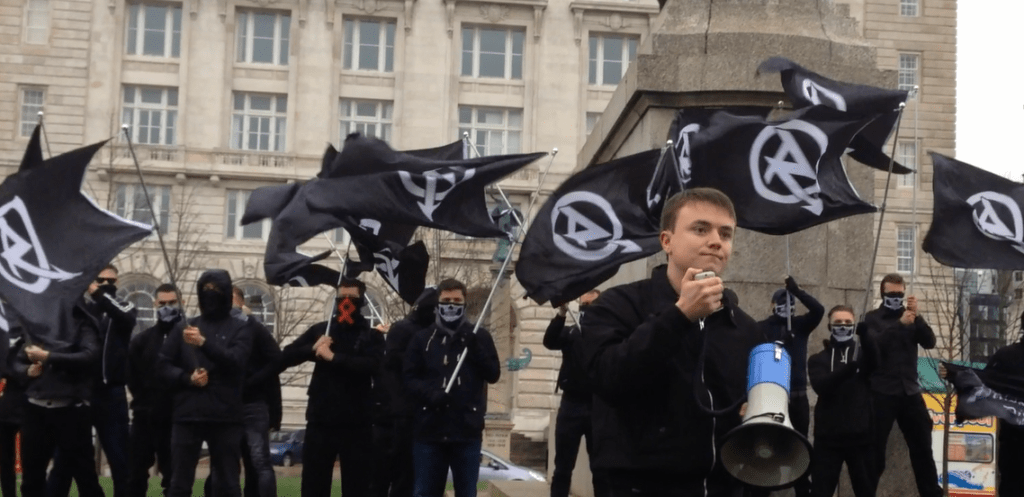 National Action member Jack Renshaw is holding a megaphone at a National Action demonstration. There are many members of National Action behind him, all dressed in black, covering their faces and waving the national action flag