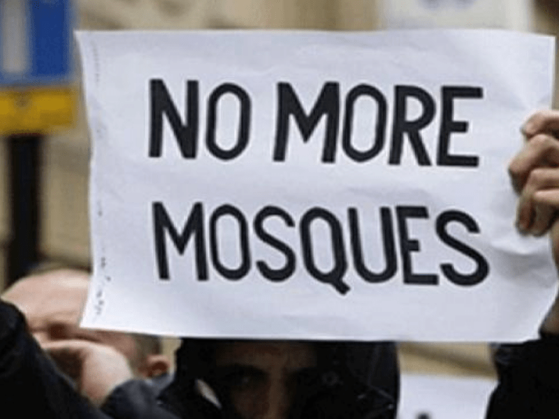 """someone holding a placard which says """"no more mosques"""""""