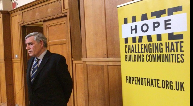 Gordon Brown standing in front of a HOPE not hate banner