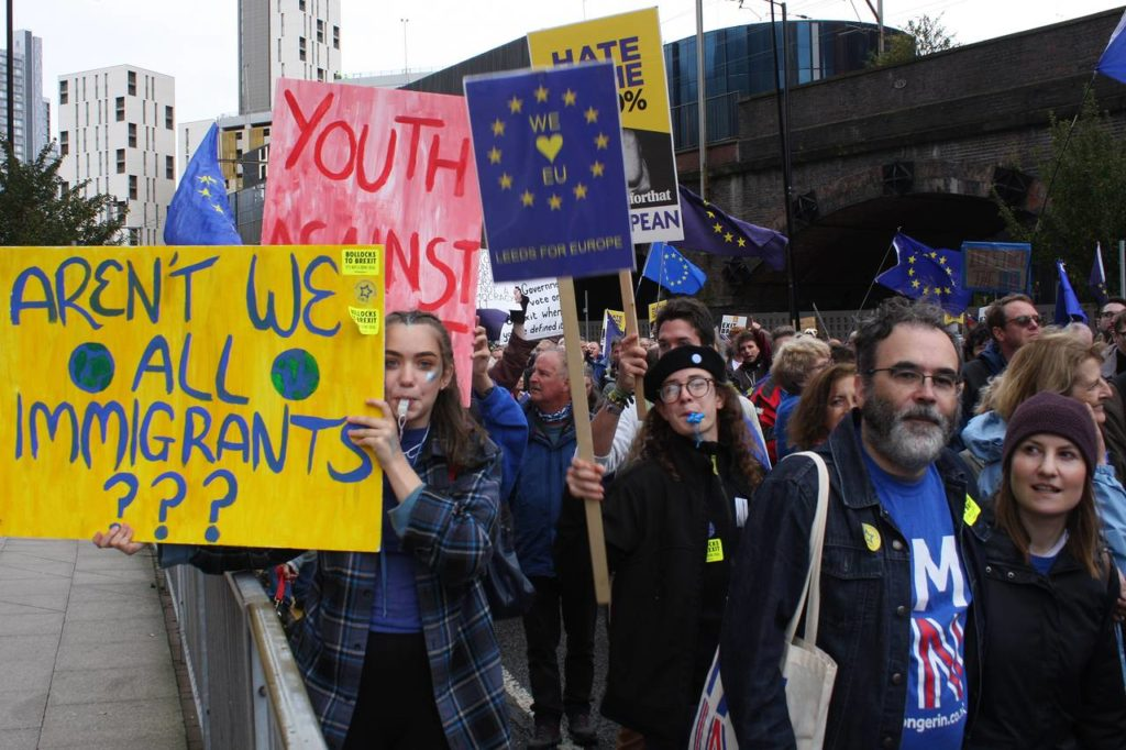 """a group of people protesting to stay in the EU. One Placard reads: """"Aren't we all immigrants?"""""""