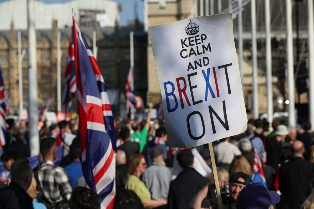 """a protest with a placard that says """"Keep calm and Brexit on""""."""