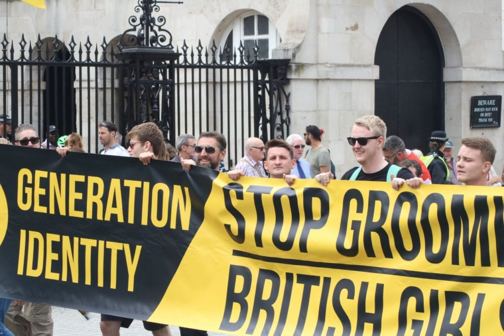 """Members of Generation Identity UK holding a banner. Banner says """"Stop grooming British girls."""""""