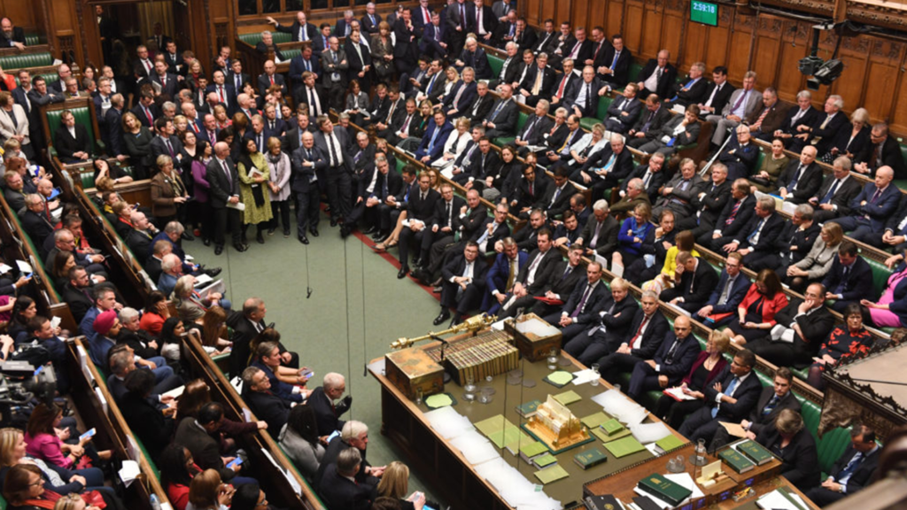 A packed House of Commons with MPs sitting on both sides of the bench