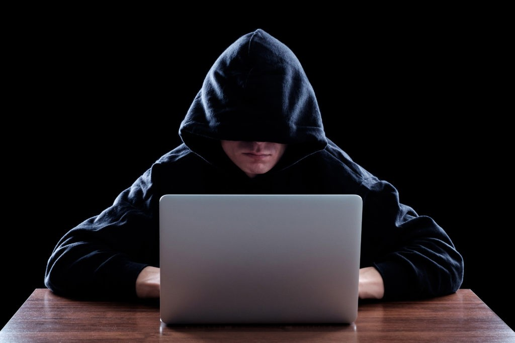 Hacker in a dark hoody sitting in front of a notebook. Cybersecurity concept. Dark background