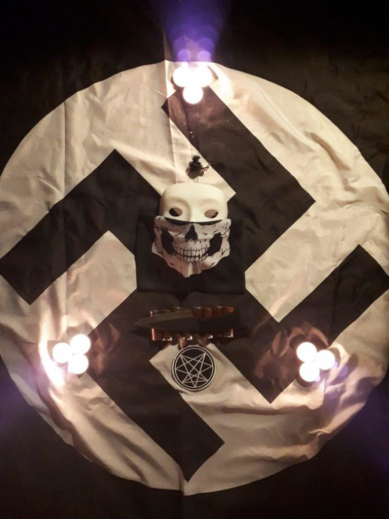 a white swastika with a menacing-looking skull in the middle