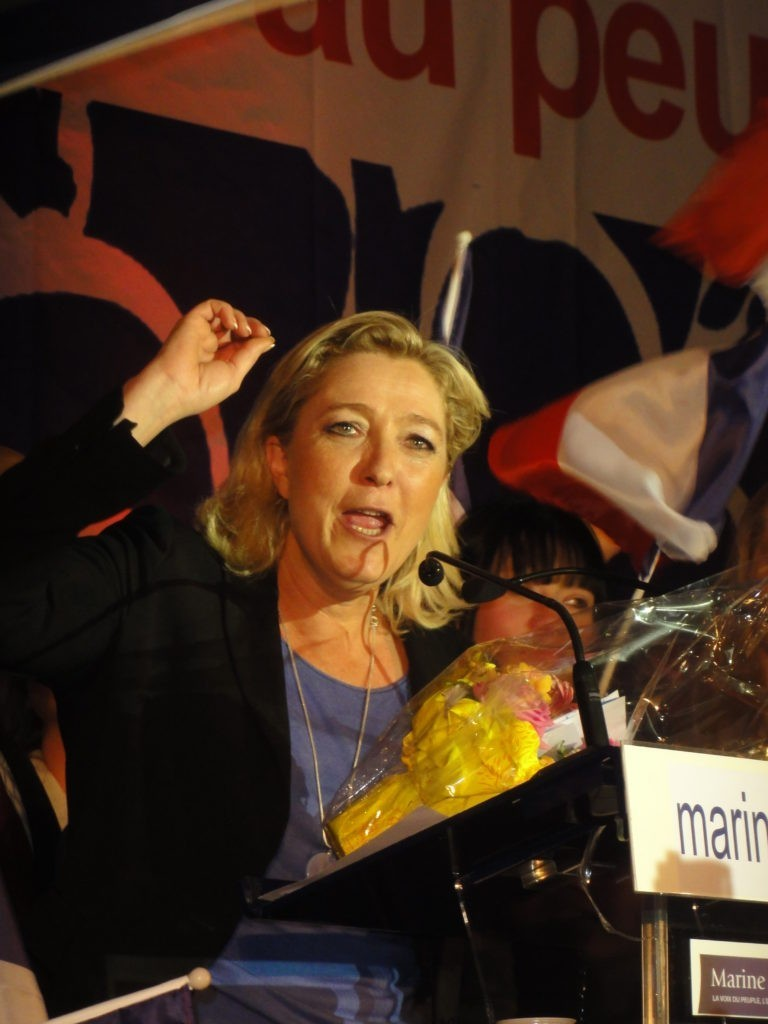 Marine Le Pen behind a podium giving a speech