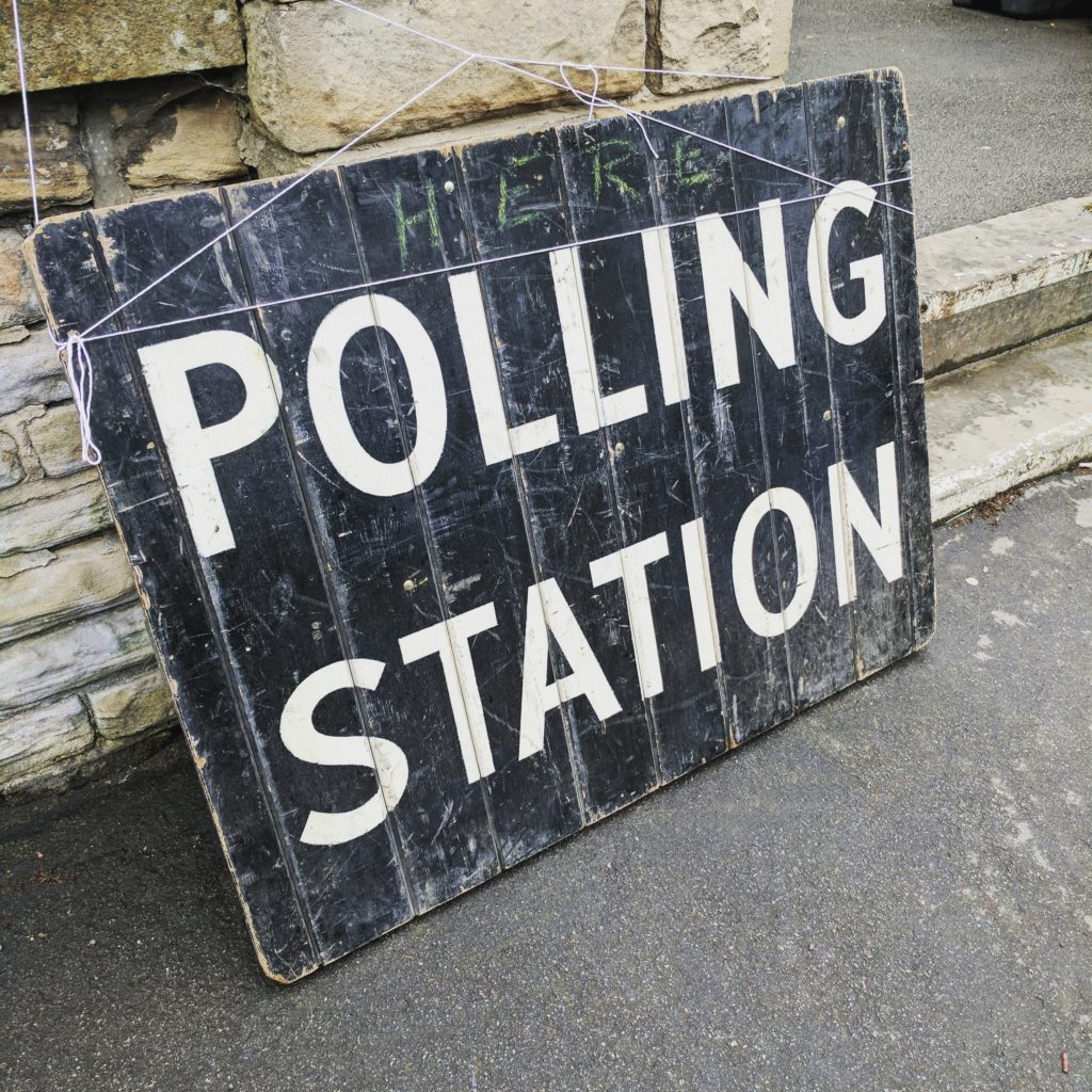"""a wooden sign on the floor which says """"polling station"""""""