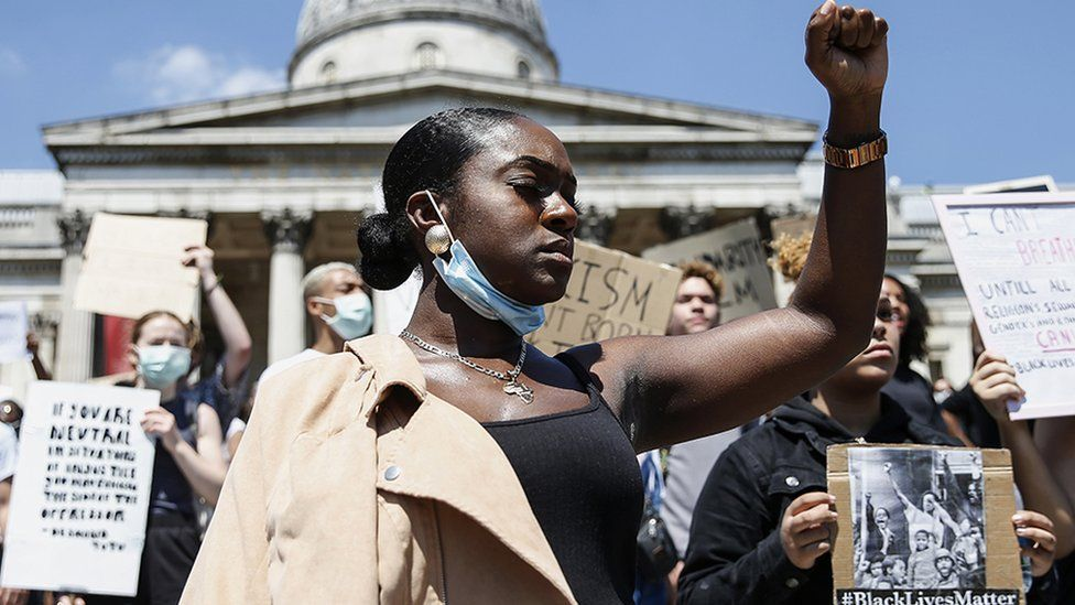 A woman has her fist held up while protesting at the BLM march, London 2020.