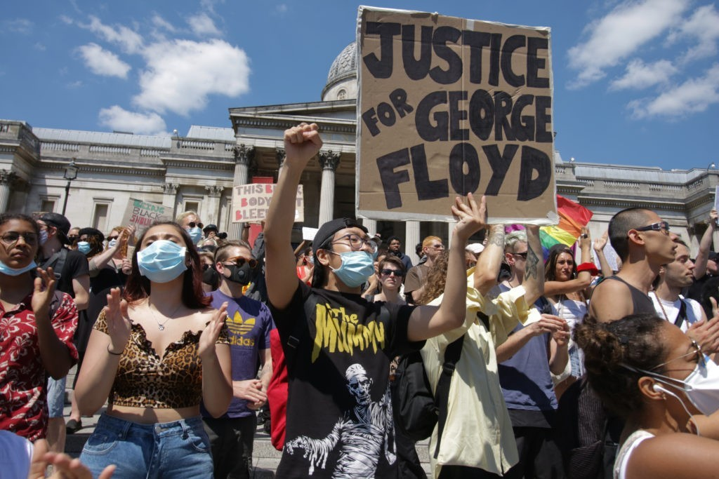"""Numerous of people taking part in last year's Black Lives Matter protest outside Trafalgar Square, London. A man is holding a sign that says """"Justice for George Floyd"""""""