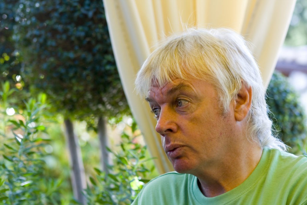 A side profile of David Icke sitting down