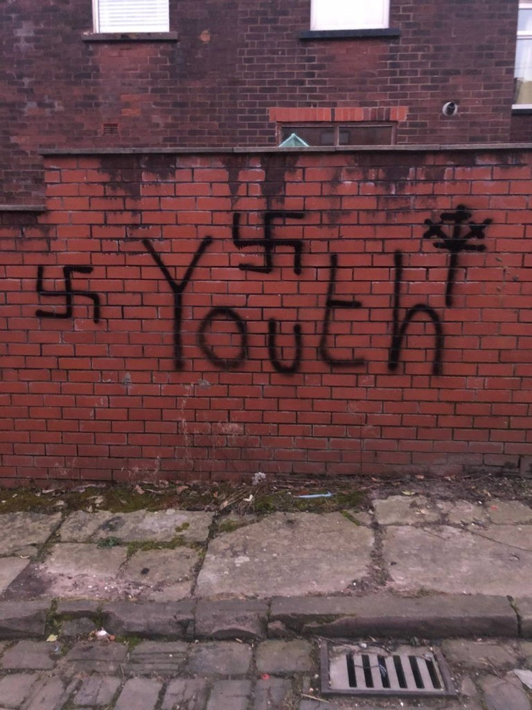 3 swastika's have been graffitied onto a wall. The word 'youth' written below the nazi symbol