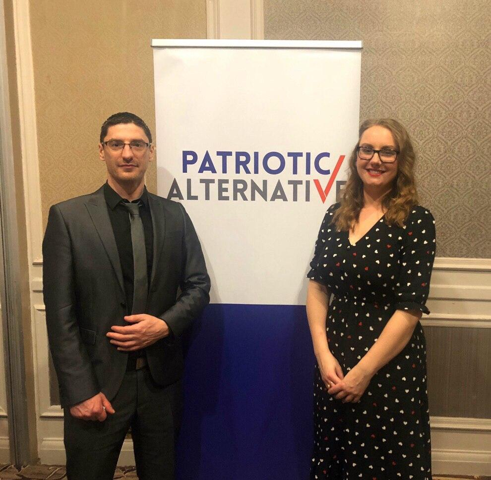 A man and a woman standing in front of a Patriotic Alternative sign