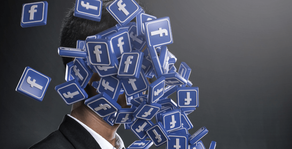 Man looking at phone which is emitting a cascade of Facebook branded F blocks